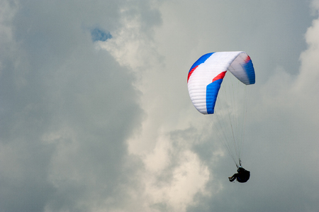 Alone paraglider flying in the blue sky against the background of clouds. Paragliding in the sky on a sunny day. 写真素材