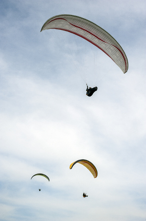 Three paragliders flying in the blue sky against the background of clouds. Paragliding in the sky on a sunny day. 写真素材