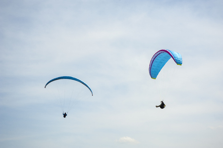Two paragliders flying in the blue sky against the background of clouds. Paragliding in the sky on a sunny day. Stok Fotoğraf