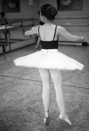 Ballerina are dancing in the dance hall. Close-up of a ballerina in the dance hall. Black and white photography.