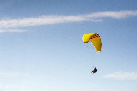 Alone paraglider flying in the blue sky against the background of clouds. Paragliding in the sky on a sunny day. 版權商用圖片