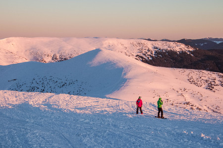 Snowboarders on top of a mountain at sunrise on a frosty winter morning. Snowboarders on the mountain in the Carpathians are preparing for the descent and freeride.