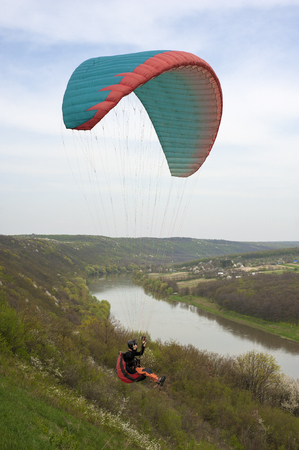 Paraglider flies over the river and the blooming mountainside in the spring season. Paragliding over the spring fields and meadows near the Dniester River in Ukraine. Фото со стока - 121033208