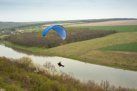 Paraglider flies over the fields and the blooming mountainside in the spring season. Paragliding over the spring fields and meadows near the Dniester River in Ukraine. Фото со стока