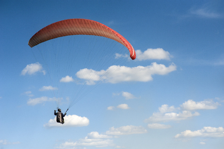 The red paraglider is flying against the background of the clouds. Paragliding in the sky on a sunny day.