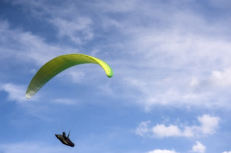 Yellow and green sky background. Paragliding in the sky on a sunny day.