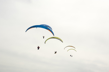 Group of paraglider flying against the background of clouds. Paragliding in the sky on a sunny day. Фото со стока