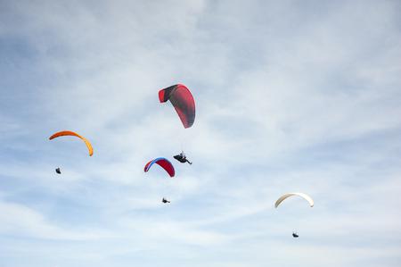 Gruppe von Gleitschirmfliegen vor dem Hintergrund von Wolken. Gleitschirmfliegen am Himmel an einem sonnigen Tag.