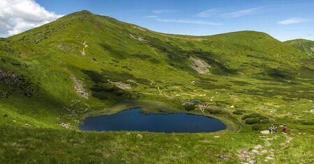 Lake Nesamovite in the Carpathians in the summer sunny day. Alpine season Amazing mountain landscape in mountain valley. Montenegrin Range in the Carpathians. Stock Photo