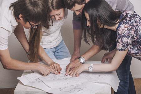 白い部屋のテーブルの上の図面で働く人々 写真素材