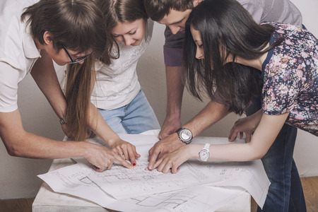 People who work with drawings on the table in the white room Foto de archivo