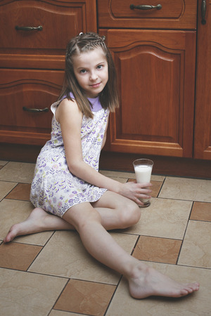 girl socks: The girl child with a glass of milk sitting on the floor