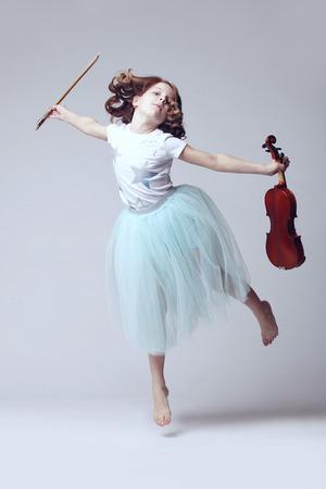 白い背景のヴァイオリンと女の赤ちゃん