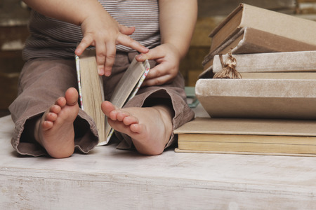 reading: Small feet of a child watching a book Stock Photo