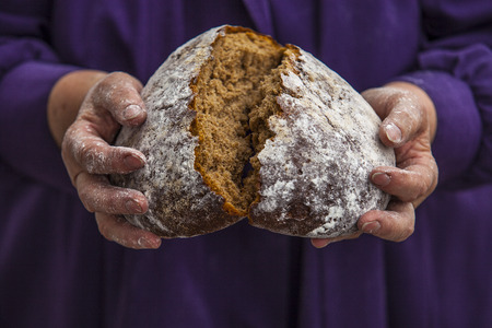 loving hands: An elderly woman model with black bread in loving hands Stock Photo