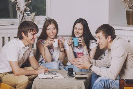 Vrienden thuis en communiceren via het proces van het drinken van thee op de bank