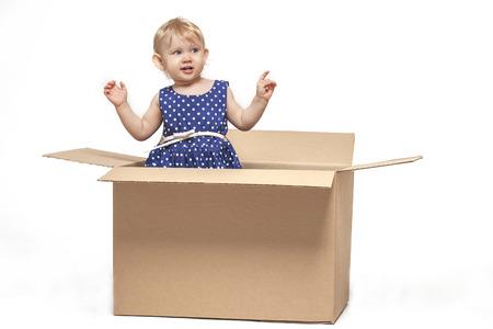 Een klein kind in kartonnen dozen op een witte achtergrond