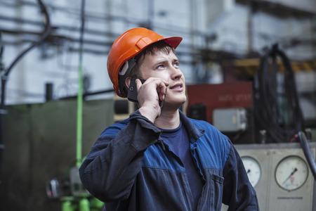 De jonge man aan het werk op de oude fabriek aan de installatie van de apparatuur in een beschermende helm Stockfoto