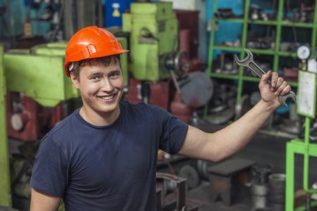 保護用のヘルメットで機器のインストールの古い工場で働いて若い男 写真素材
