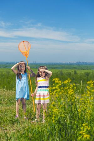 Kids summer in the meadow with orange net in the sky photo