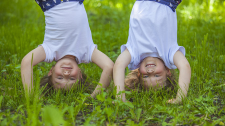 Children standing in a meadow on the hands on the green grass 写真素材