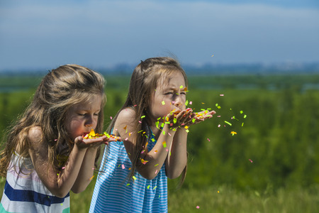 inflate: Children with confetti in hand inflate them in the wind against the sky