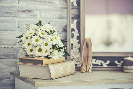 wedding reception: Wedding bouquet of daisies on a stack of books on a shelf Stock Photo