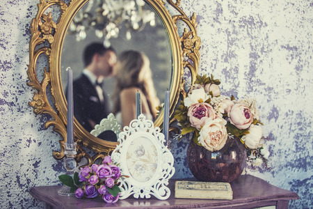 Vintage mirror with the bride and groom in the reflection on the wedding day