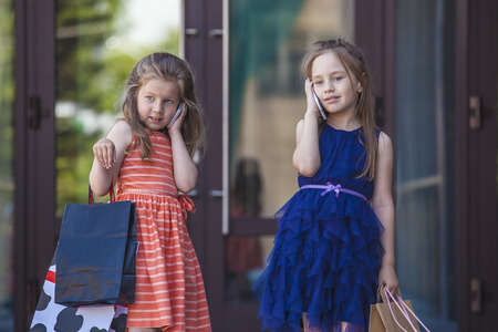 petite fille avec robe: Enfants de dames de filles au milieu du centre commercial dans la ville