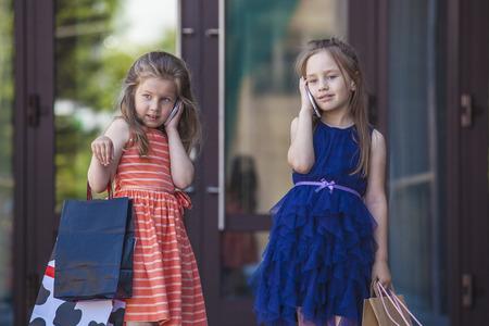 niños de compras: Los niños de las señoras de las muchachas en medio del centro comercial de la ciudad