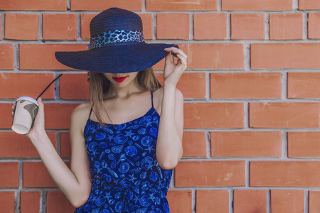 red and blue: Model woman with Cup of coffee in wicker hat on wall background