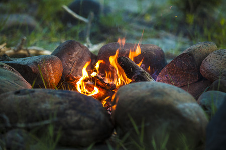 ring light: Tourist bonfire at dusk in the forest framed by stones Stock Photo