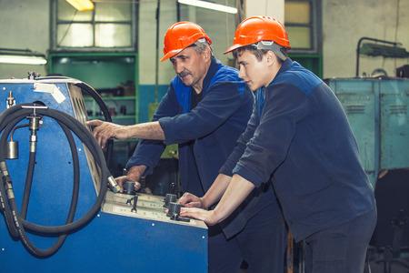 protective helmets: Uomini lavorano sulla vecchia fabbrica per l'installazione di apparecchiature in caschi protettivi