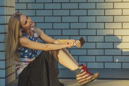 Female model on the background of a city building in a t-shirt with an American flag and a phone