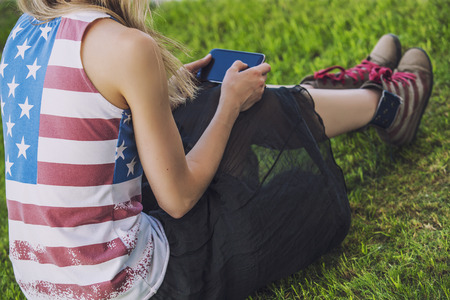 Vrouwelijk model tegen een groene gazon in een t-shirt met een Amerikaanse vlag en een telefoon Stockfoto