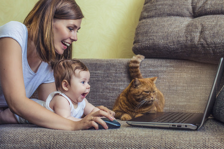 The woman with a baby and a cat at the laptop lying on the couch Reklamní fotografie