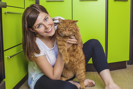 The woman with a ginger cat in her arms cuddling on the bright kitchen