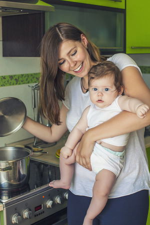 happier: The mother of a woman with a baby cooks the food in a pot on the stove Stock Photo