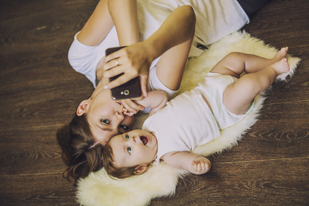 Woman with a baby doing a selfie lying on wooden floor Reklamní fotografie