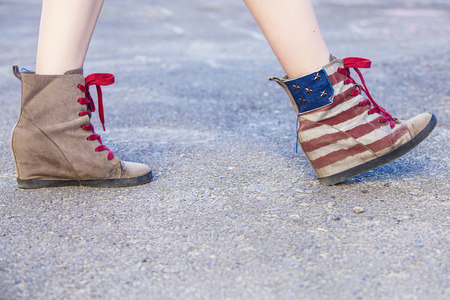 wedge: Female legs in colorful sneakers with the design of the American flag on the grass