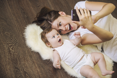 Woman with a baby doing a selfie lying on wooden floor Banque d'images