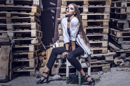 street shot: Full-length portrait young elegant woman in the gray jacket, pants and shoes with heels on a wooden chair casual style . Fashion street shot. Stock Photo