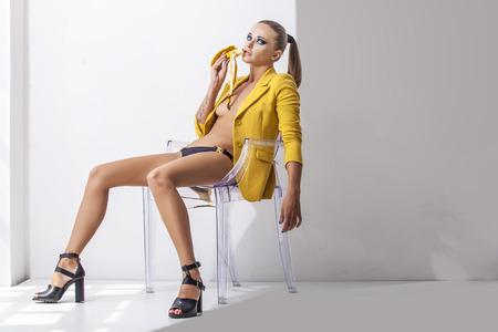 Full-length portret jonge elegante vrouw in de gele jas, broek en schoenen met hakken op een transparante stoel met banaan. Fashion studio-opname.