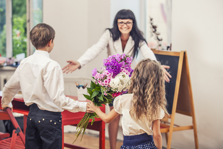 profesor alumno: Muchacho y muchacha ni�os dan flores como un maestro de escuela en el d�a del profesor. El d�a de los conocimientos, la educaci�n, el aprecio, la generaci�n. Foto de archivo