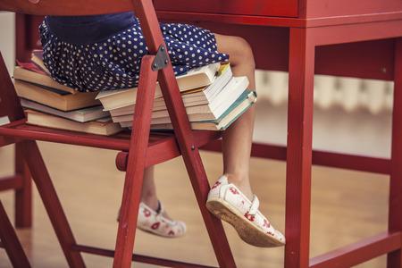 Meisje, zittend op de stoel en op de boeken op school in de klas. Lichaamsdelen, training, opleiding, kleuterklas, zullen groeien.