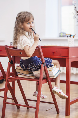 year increase: Little girl sitting on the chair and on the books at school in class. Training, education, preschool, will grow. Stock Photo