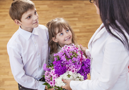 female teacher: Boy and girl children give flowers as a school teacher in teachers day. The day of knowledge, education, appreciation, generation. Stock Photo