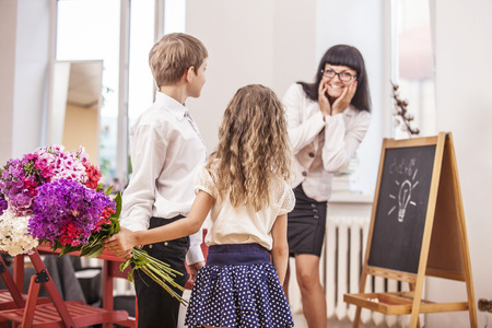 Boy and girl children give flowers as a school teacher in teachers day. The day of knowledge, education, appreciation, generation. Stock Photo