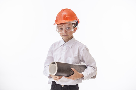Boy child in a protective helmet and goggles with a construction drawing. Studio, isolated, Builder, white.