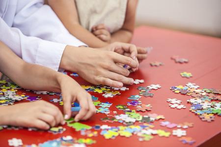 solucion de problemas: Los niños, amigos manos ensamblan el rompecabezas en el color de la tabla. Conexión, rompecabezas, la amistad, la Unión. Foto de archivo